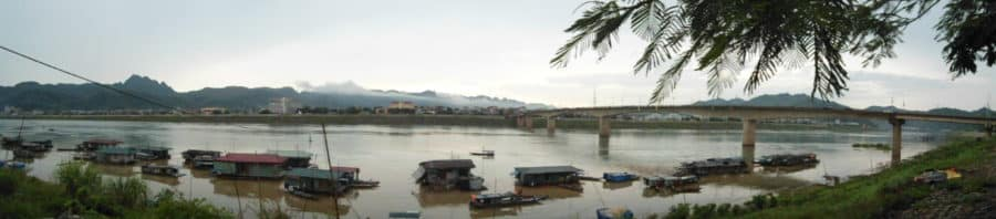 A panorama of house boats floating next to a bridge on the Song Da river in Hoa Binh