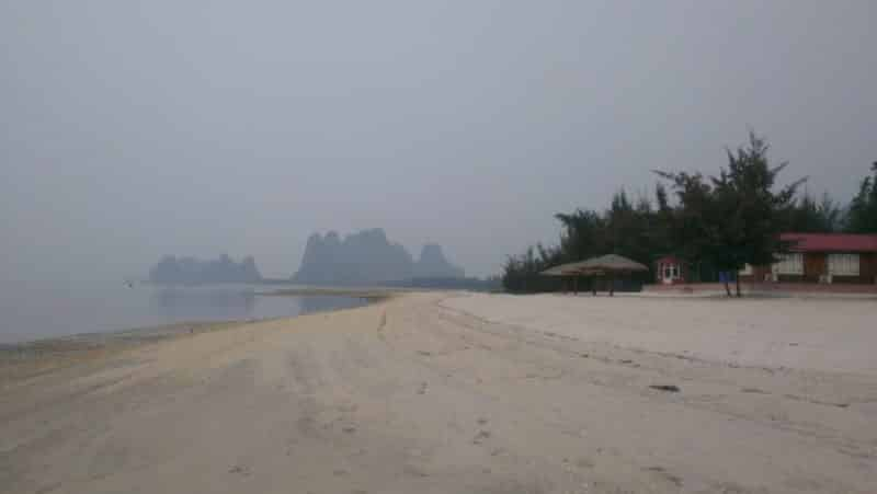 A sabdy beach with karst peaks in the background at Van Don Peninsular, north of Halong Bay