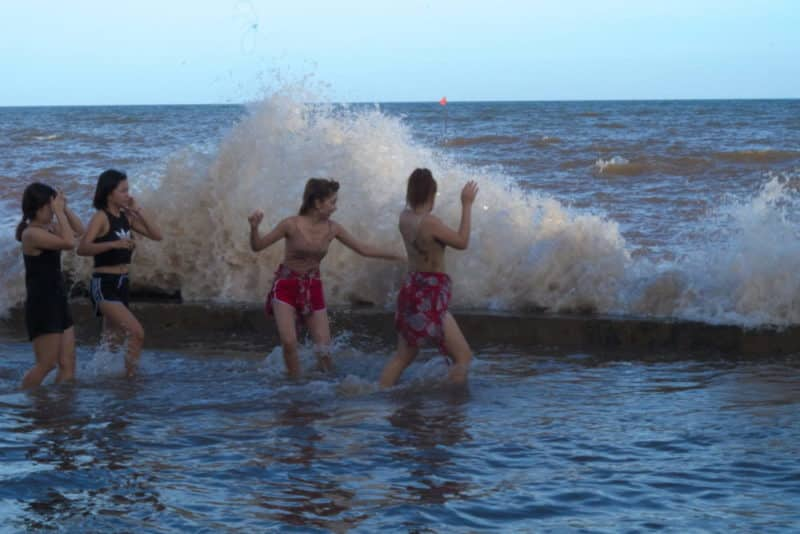 Waves crashing into girls swimming at king tide on the coast of Nam Dinh in Vietnam