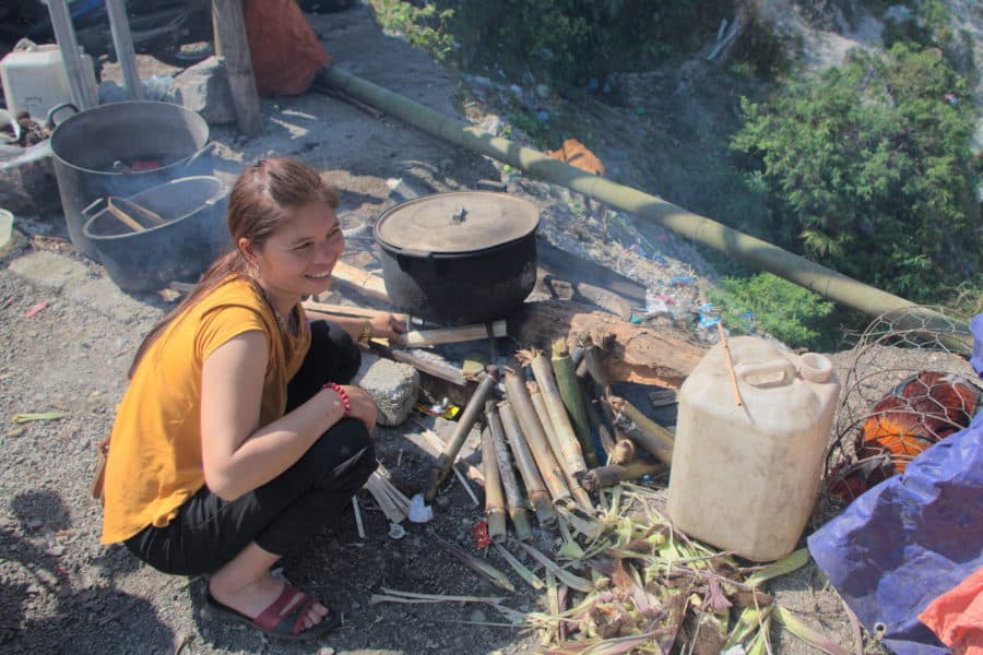 A Muong lady cooking on Thung Khe mountain pass where tourists stop to rest