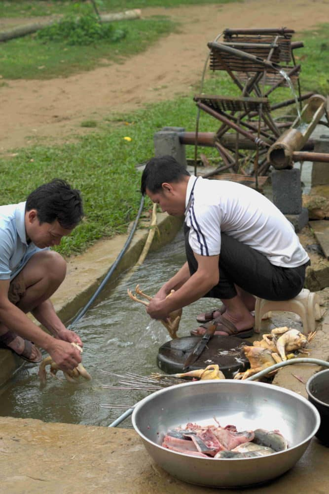 Men washing chicken and fish in a freshwater stream