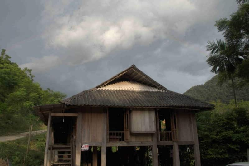 A Muong minority stilt house with a rainbow above it
