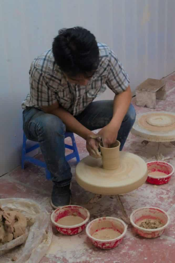 Man making a clay vase on a pottery wheel in Vietnam