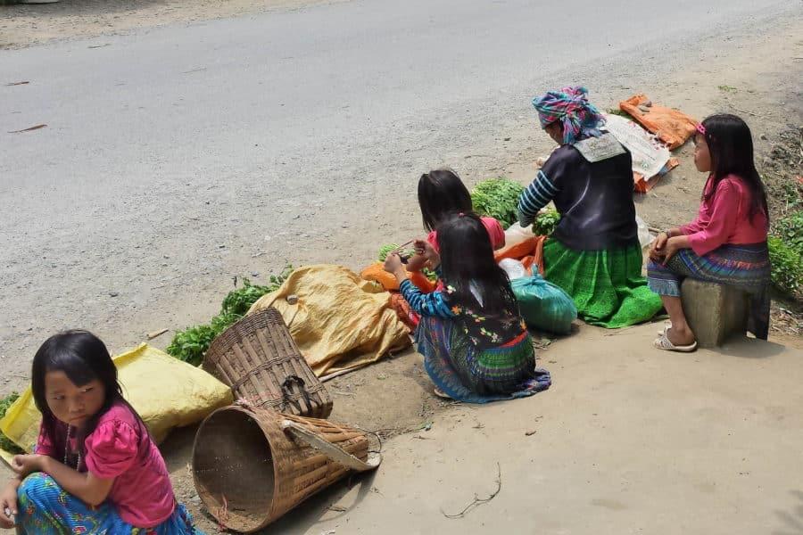 Ethnic minority girls selling vegetables on the side of the road
