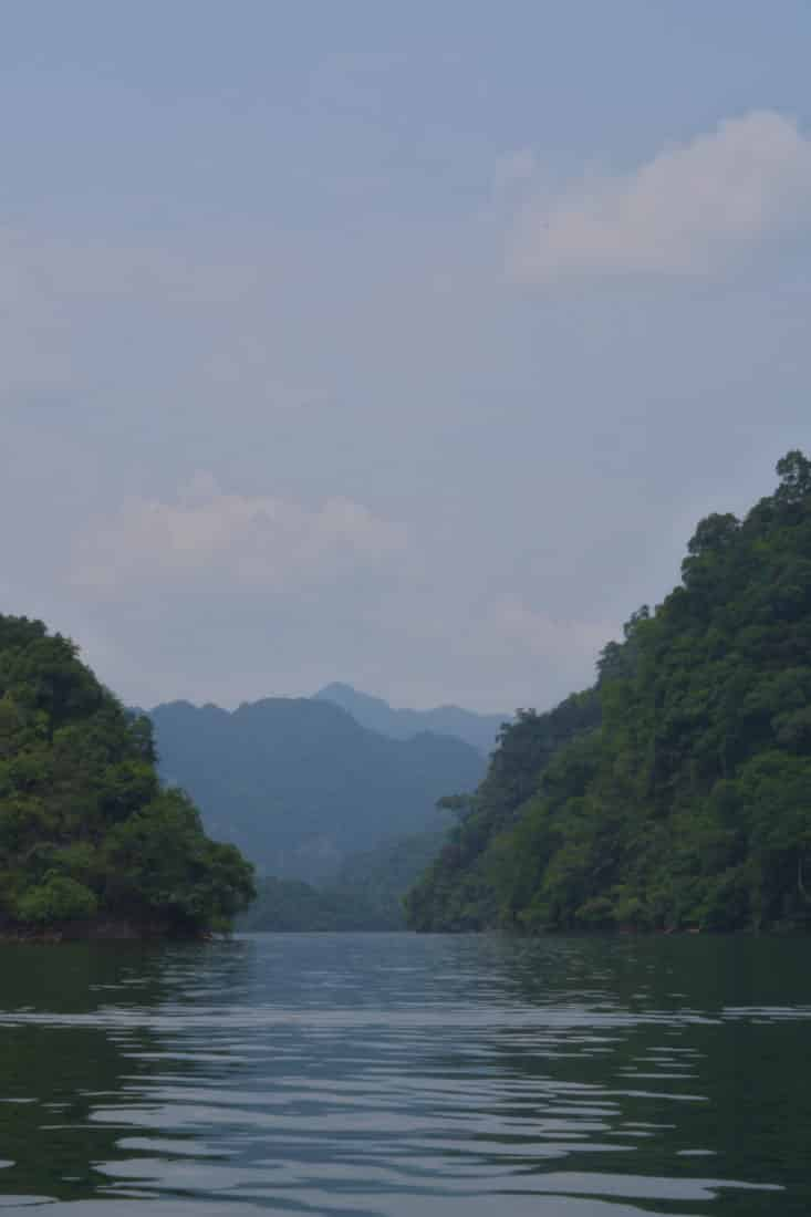 A view of Ba Be lake from a boat tour as it's still waters are wedged between lush green mountains.