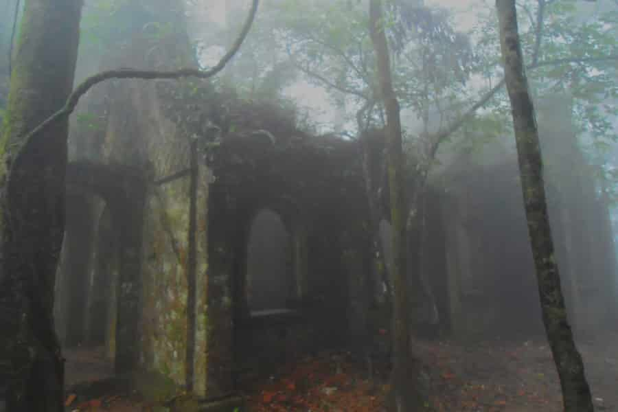 Stone church ruins surrounded by fog and trees in winter