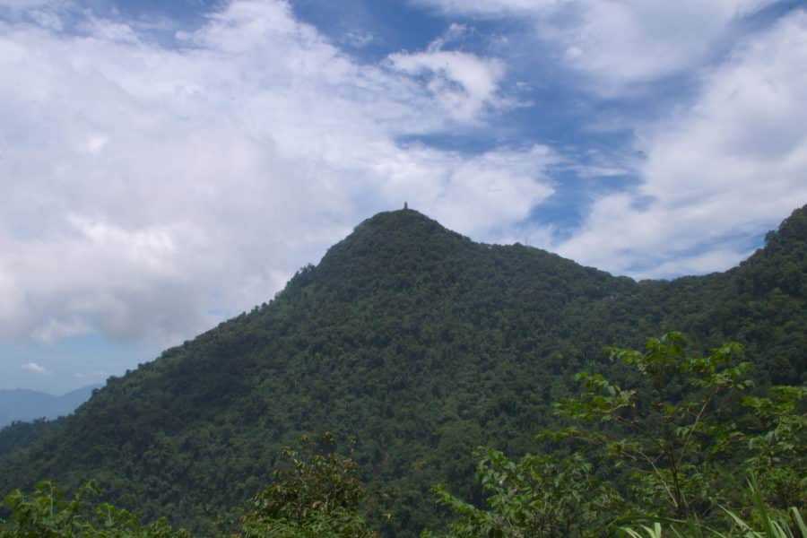 A forested hill topped with a pagoda at its summit