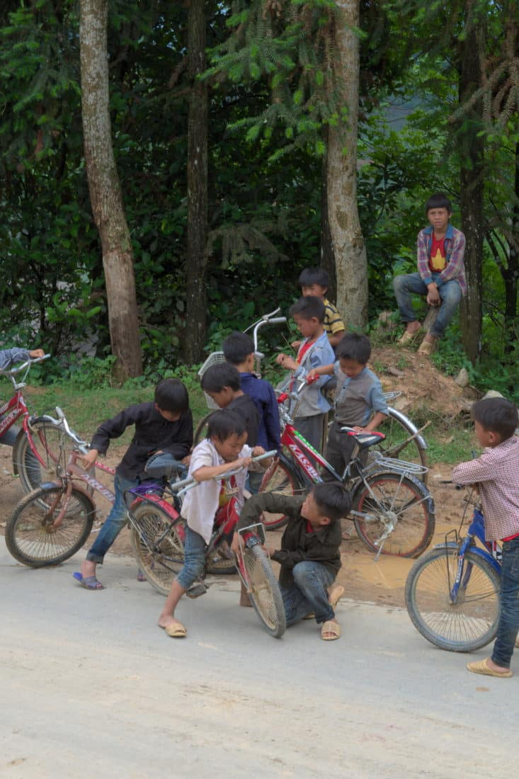 passing children with bicycles on a viet tracks motorbike tour
