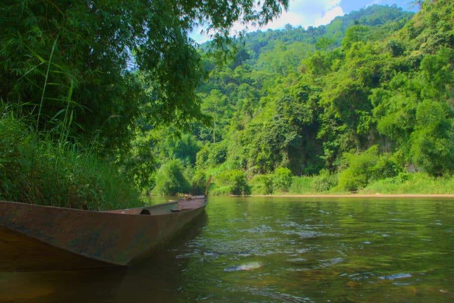 A wooden canoe floatingon a peaceful stream at the edge of Ba Be lake