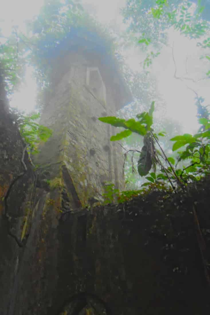 Looking up through the fog at a ruined French colonial church tower in the jungle of Ba Vi mountain