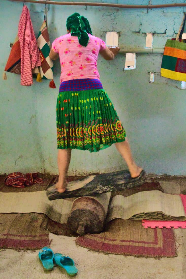 A woman standing on a plank and log rolling side to side in order to soften fabric underneath