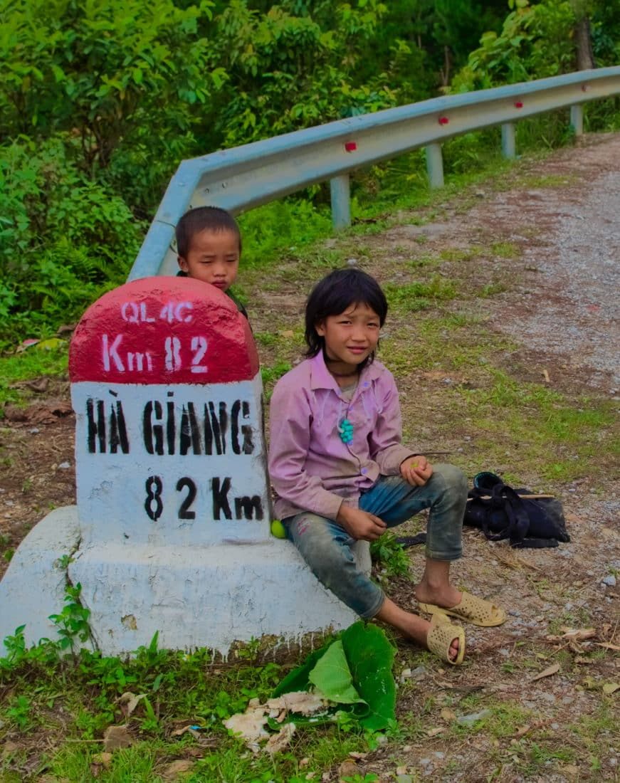 Two Vietnamese boys sitting next to a Ha Giang road marker on a motorbike tour