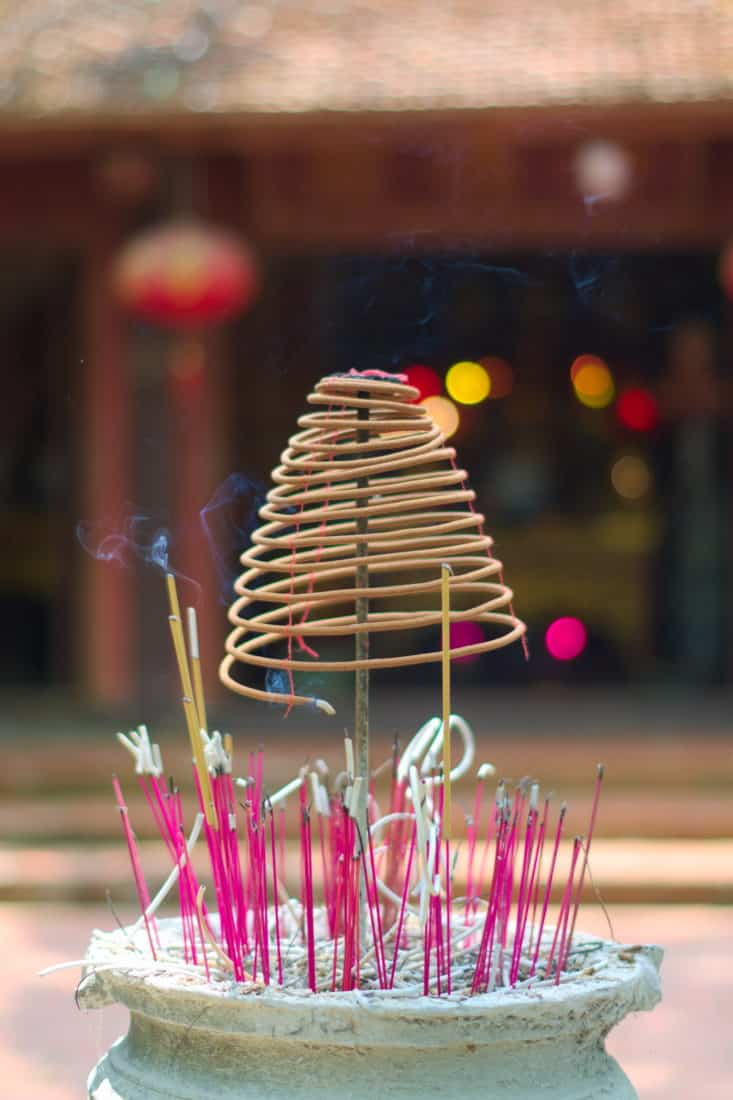 Sticks and a spiral of incense burning in front of a traditional temple asan offering
