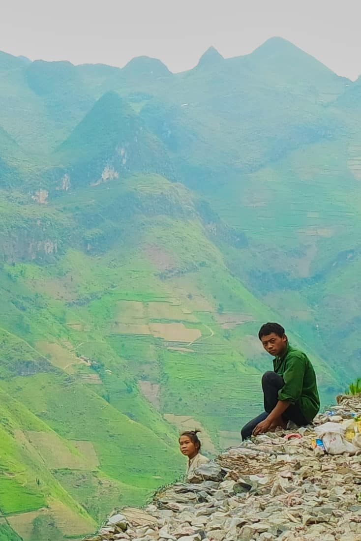 A man sitting on the edge of a cliff road with mountains behind him at Ma Pi Leng pass, Ha Giang