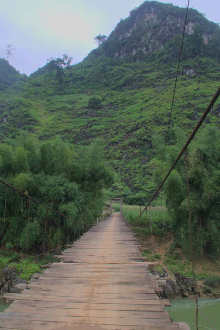 Wood planked suspension brige over a river we cross on a ha giang motorbike tour