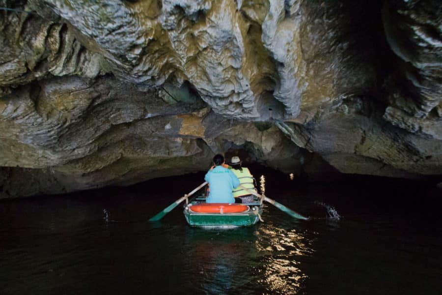 A boat ebtering a low cave in Trang An, Ninh Binh