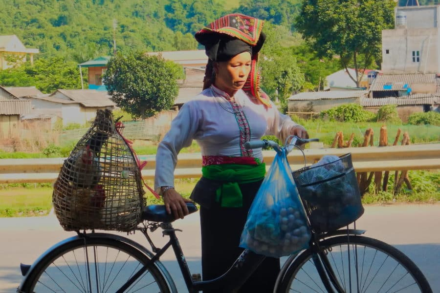 A minority lady selling food by bicycle in Son La, Vietnam during a motorbike journey