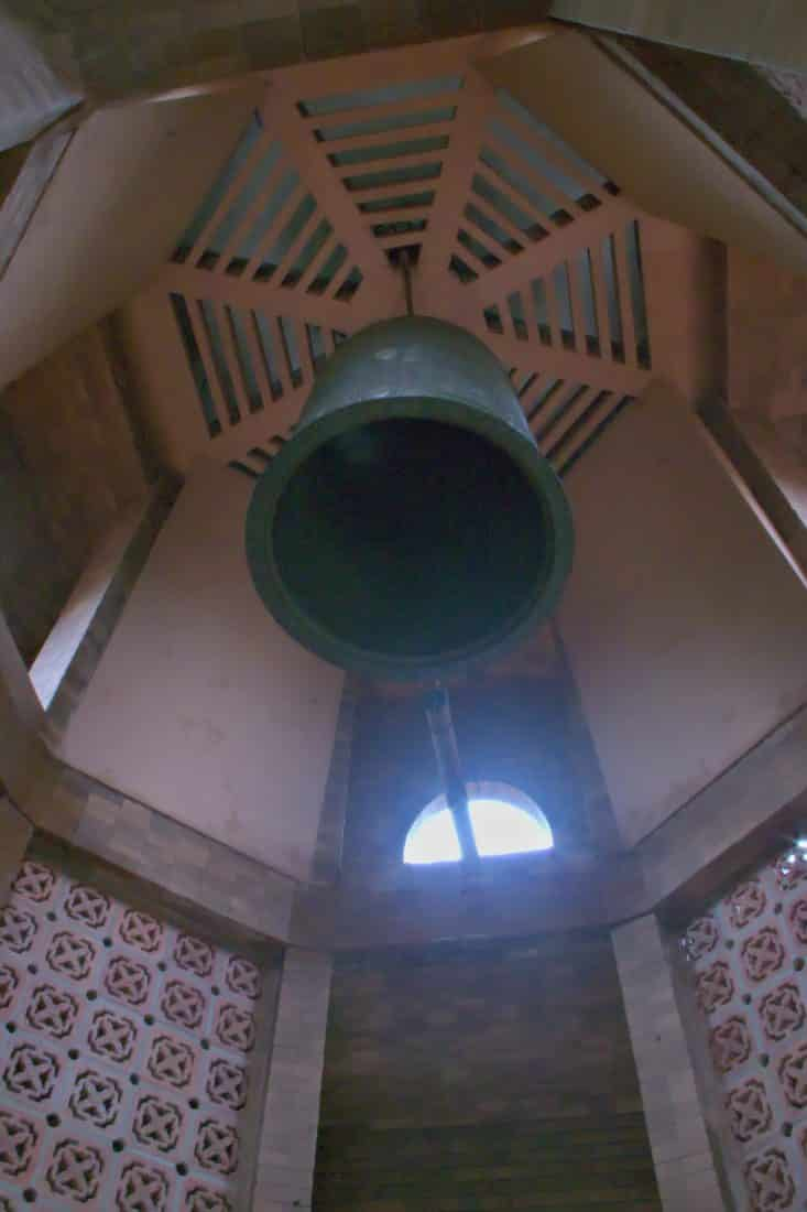looking up at a giant bell inside a vietnamese stupa