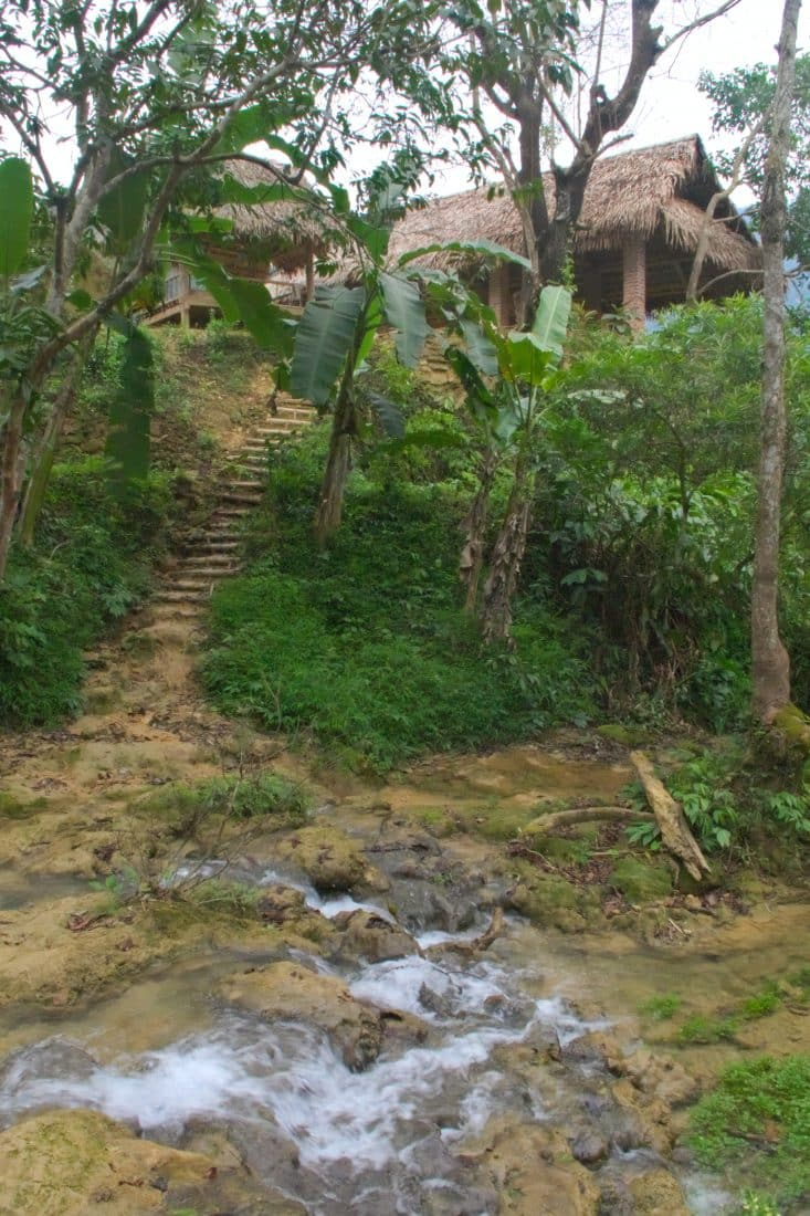 A wooden hut across a stream in the jungle of Vietnam
