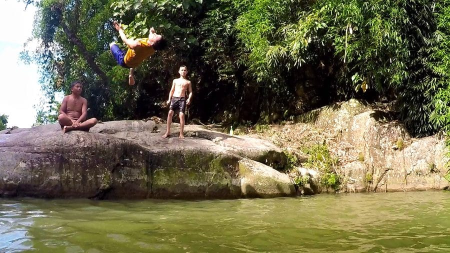 A man doing a backflip of a rock into water