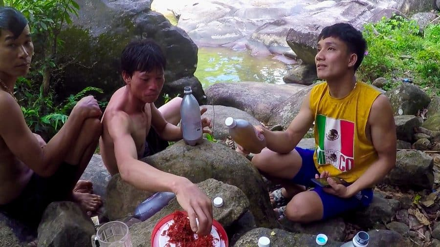 Vietnamese men drinking beer on rocks beside a stream