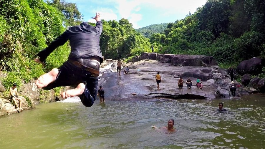 A man jumping into a stream with jeans on in Vietnam