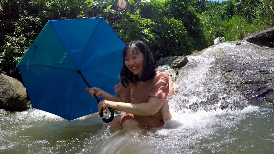 A vietnamese girl with a blue umbrella bathing in a waterfall
