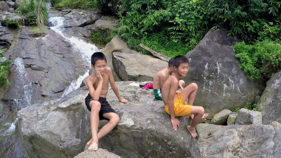 3 Vietnamese boys sitting on a rock at a waterfall