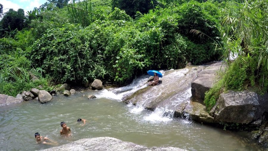 people swimming in a waterfall pool in ba be lake area of Vietnam