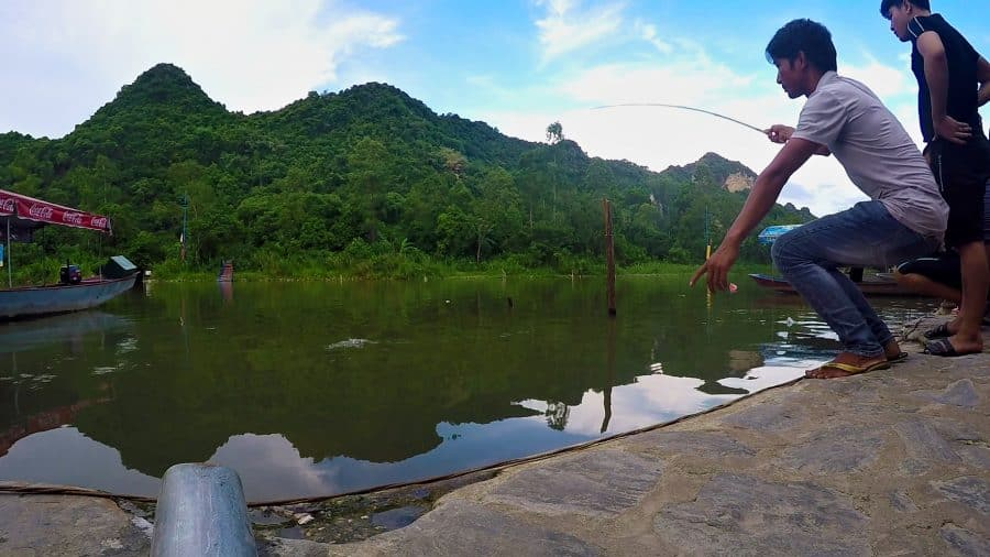 A man catching a fish with a small bamboo rod in Vietnam