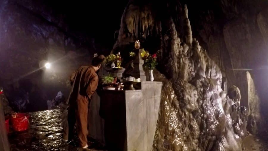 A vietnamese monk at a buddhist cave altar