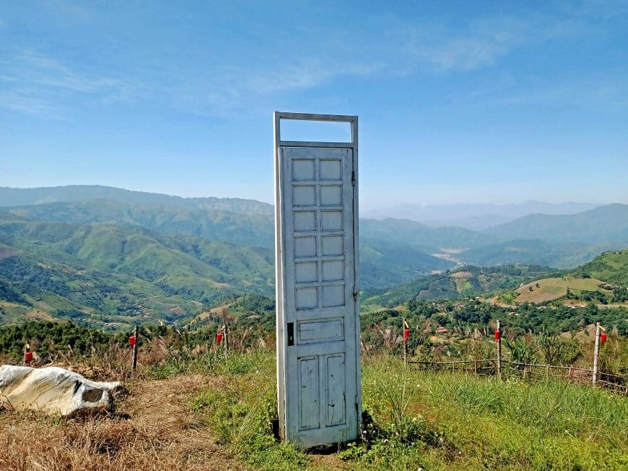 A mountain view with a door prop for photographs on the top of Pha Din pass