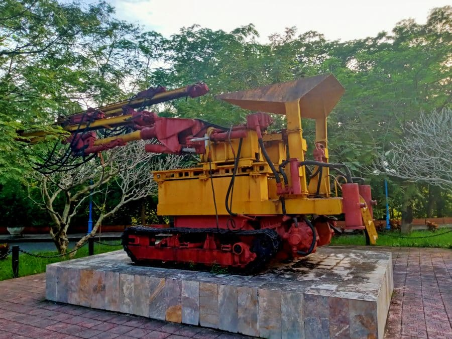 An old red and yellow drilling rig on display in a park