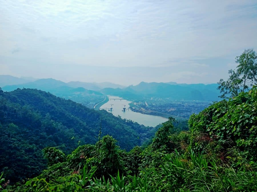 A view of a river in the distance surrounded by green mountains